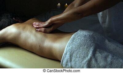 Shot of a professional masseuse massaging back and shoulders...