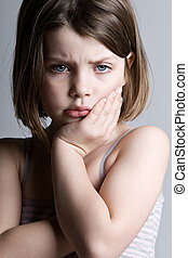 Sad Looking Child against a Grey Background