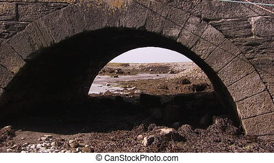 Shot of a small arch under an old bridge - Shot of a small...