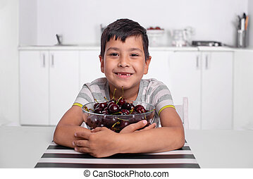 Shot of a smiling boy sitting in the kitchen and hugging a large bowl of cherries.
