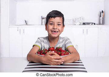 Shot of a smiling boy sitting in the kitchen and hugging a large bowl of strawberries and cherries.