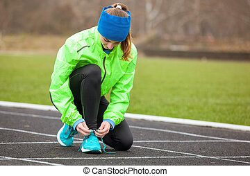 Shot of a woman tying her shoelaces on running shoes.