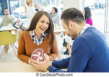 Shot of a young man surprising his girlfriend with a gift