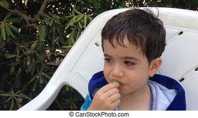 Adorable kid eating grape - Shot of Adorable kid eating...