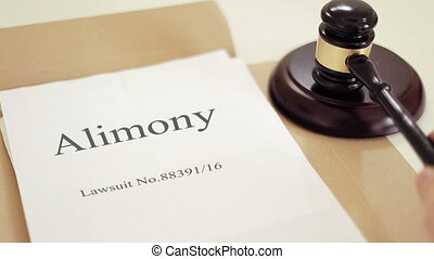 Alimony verdict on lawsuit folder with gavel placed on desk of judge in court