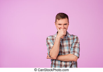 Shot of attractive young caucasian man looking at camera with cunning funny expression, closing his mouth