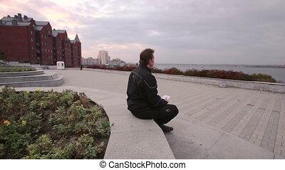 man sitting near the river - shot of camera on crane. man...