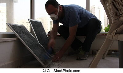 cleaning dust from air conditioner filters - Shot of...