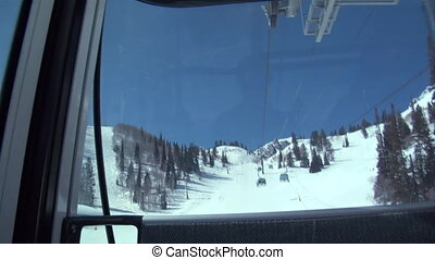Shot of enclosed chairlifts passing, blue sky