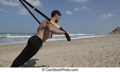 Shot of Fitness straps workout on the beach
