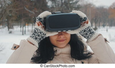 shot of girl getting experience in using VR-headset outdoor at winter park