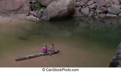 Shot of girls on a log in water near boulders