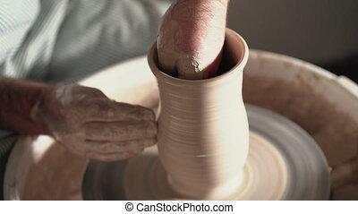 Shot of half-finished ceramic vase spinning on wheel. Close...