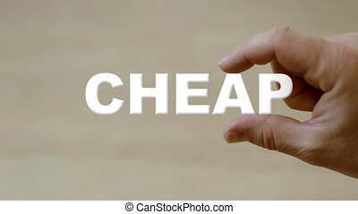 Hand holding the word cheap