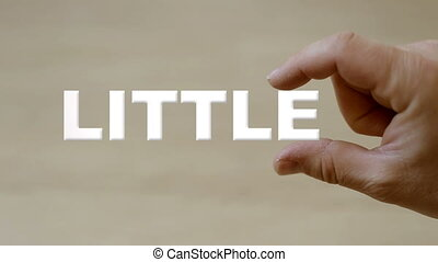 Hand holding the word LITTLE