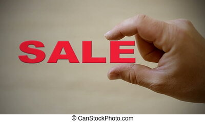 Hand holding the word SALE