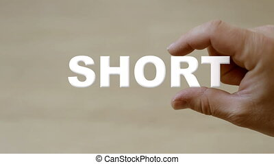 Hand holding the word SHORT