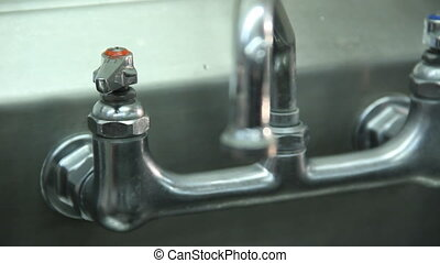 Shot of hand reaching out to turn on hot water faucet