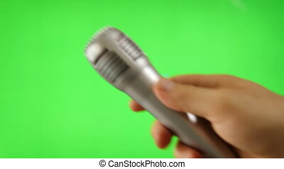 Holding Up A Microphone Isolated On Green Screen