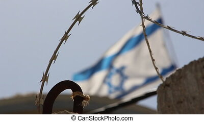 Israeli flag flying on the border with barbed wire