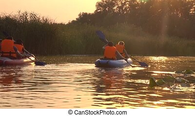 Shot of kayakers kayaking down the river i on a sunset day -...