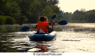 Shot of kayakers kayaking down the river in an andscape....