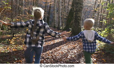 Shot of little carefree children happily running along the forest path with both their arms stretched wide open