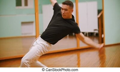 Shot of male fighter performs martial tricks with dance...