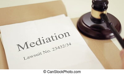 Mediation process of lawsuit folder with gavel placed on desk of judge in court