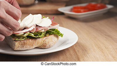 shot of mozzarella put on ciabatta bread preparing sandwich
