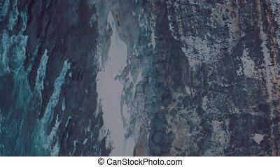 Shot of ocean waves crashing coastline cliff