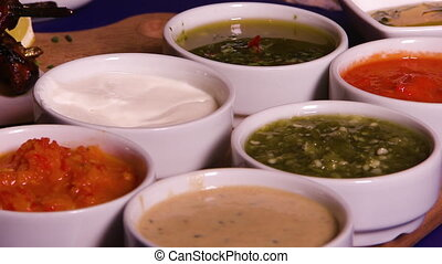 Shot of several small bowls of different sauces - Close up...