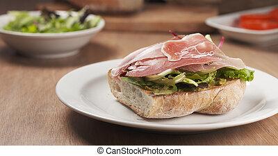 shot of speck put on ciabatta bread preparing sandwich