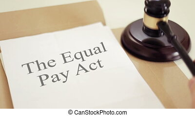 The Equal Pay Act written on folder with gavel placed on desk of judge in court