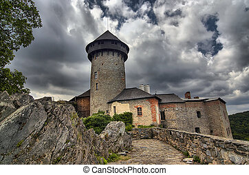 Shot of the medieval castle of the holy order of knights with omnious clouds. Czech republic, Europe.