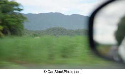 Shot of the mountain with side mirror of a car