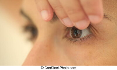 Woman placing eyes contact lenses