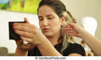 Woman tries on a designer earring - Shot of Woman tries on a...