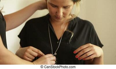Woman wears medallion necklace - Shot of Woman wears...