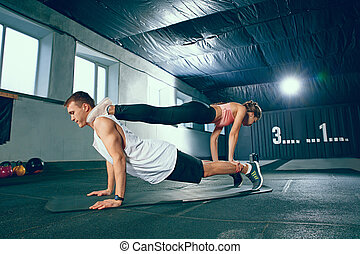Shot of young man and a woman standing in plank position at the gym