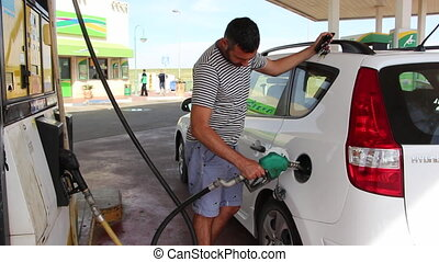 Young man filling gas into the car at a gas station - Shot...