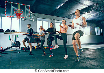 Shot of young men and a woman standing in plank position at the gym