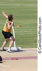 An athlete performing in the shot put event
