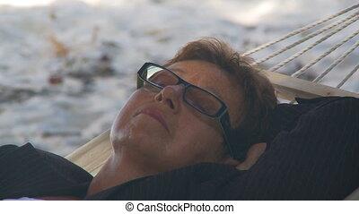 shot transition senior businesswoman sleeping in hammock