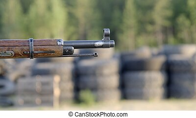 Shotgun In Man' S Hand. Front Side Of Weapon With Close Up View On Blurred Nature Background