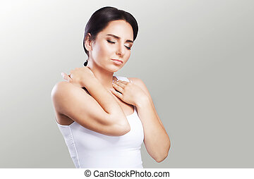 Shoulder pain. The woman holds two hands over the neck and shoulders. Dislocation. Cold. Muscle tension The concept of health. On a gray background.