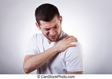 Shoulder pain - Young attractive man having shoulder pain