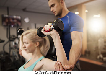 Shoulder press with a personal trainer