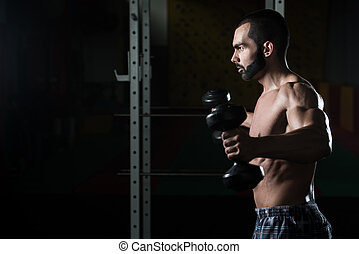 Shoulders With Dumbbells Exercise In A Gym