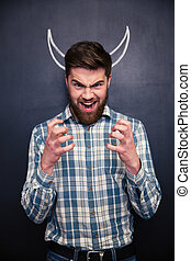 Shouting man standing over chalkboard background with drawn horns